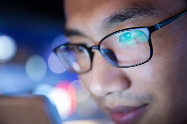 man looking at computer shows reflection of light in his glasses